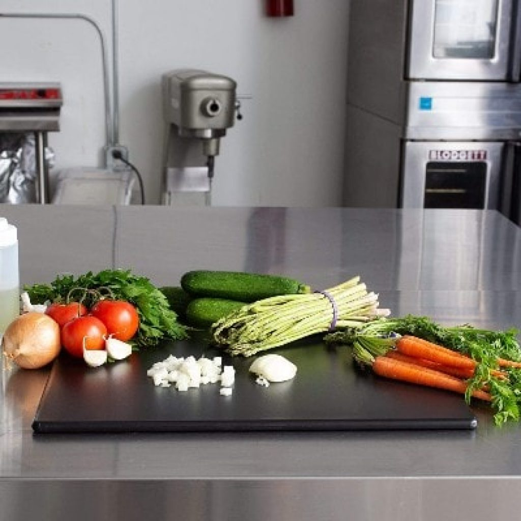 Commercial Black Plastic Cutting Board with kitchen in the background