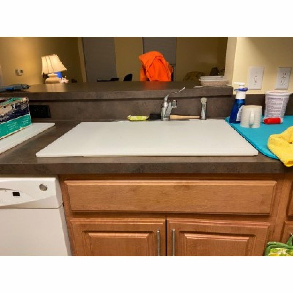 """Plastic Cutting Board 18x30 1/2"""" Thick White laying over the sink"""